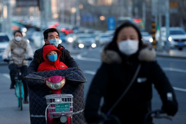 People wear masks as they ride vehicles during evening rush hour, as the country is hit by an outbreak of the novel coronavirus, in Beijing